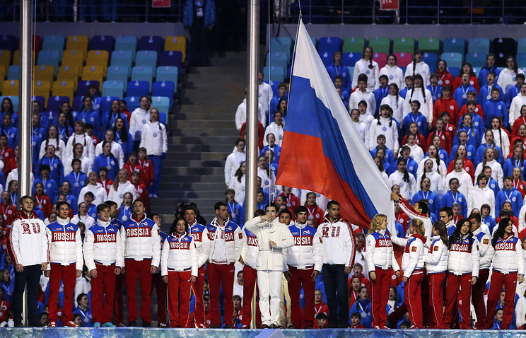 The Russian flag is raised during the closing ceremony of the 2014 Winter Olympics in Sochi
