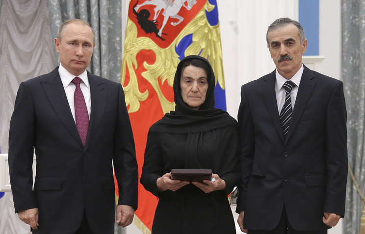 Russia's President Vladimir Putin and parents of Dagestani police officer Magomed Nurbagandov