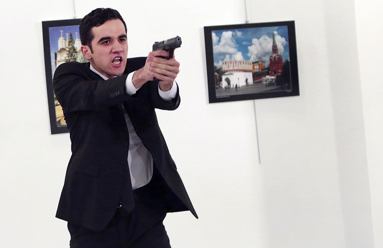 A man identified as Mevlut Mert Altintas holds up a gun after shooting Andrei Karlov