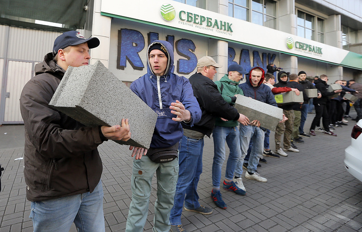 People pass stones to each other to build a wall in front of the central branch of Russian Sberbank during a protest in Kiev