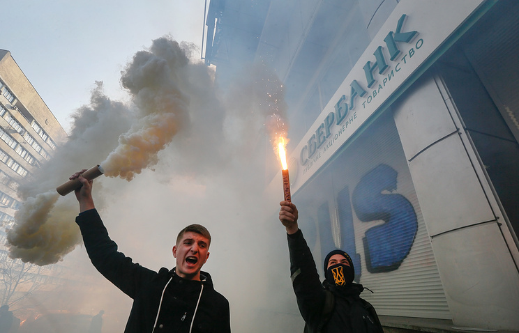 Activists burning torches in front of the entrance of the Sberbank of Russia office in Kiev, Ukraine