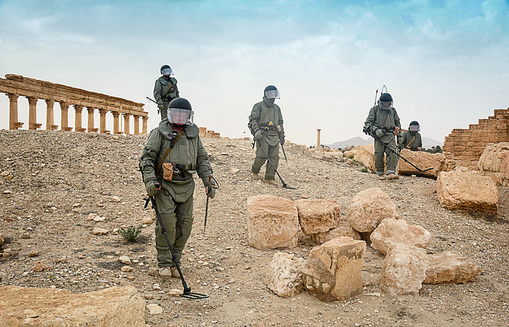 Russian military engineers use mine detectors during a mine clearing operation in Palmyra