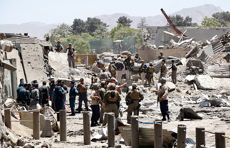 German and Afghan security officials inspect the scene of destruction caused by a suicide bomb attack in Kabul