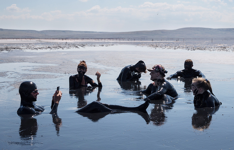 People taking a mud bath in Crimean Chokrakskoe lake