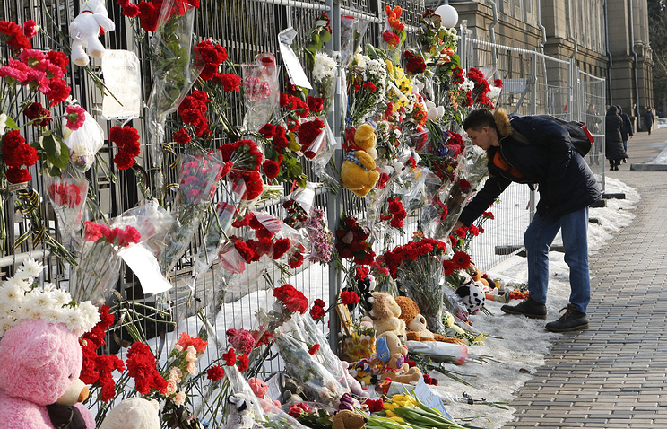 Man lays flowers to honour victims of the fire in Kemerovo near the Russian Embassy, in Kiev