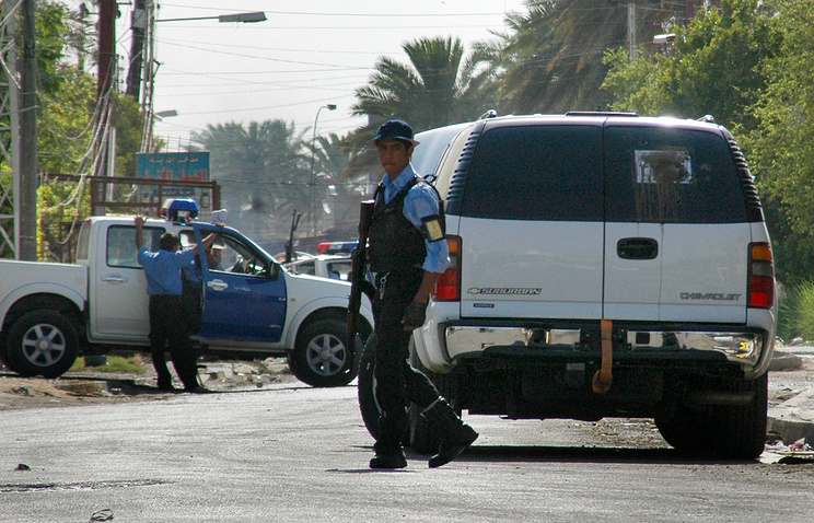 Iraqi police attend the scene of a Russian diplomatic car attacked in Baghdad's Al Mansour district, June 3, 2006