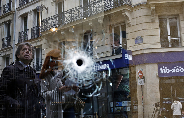A bullet hole seen on the window of a cafe in the area where the assailant of a knife attack was shot dead by police officers, in central Paris