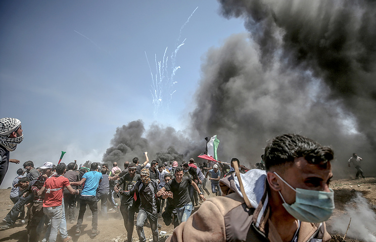 Palestinian protesters run for cover from Israeli tear-gas during clashes after protests near the border with Israel in the east of Gaza Strip