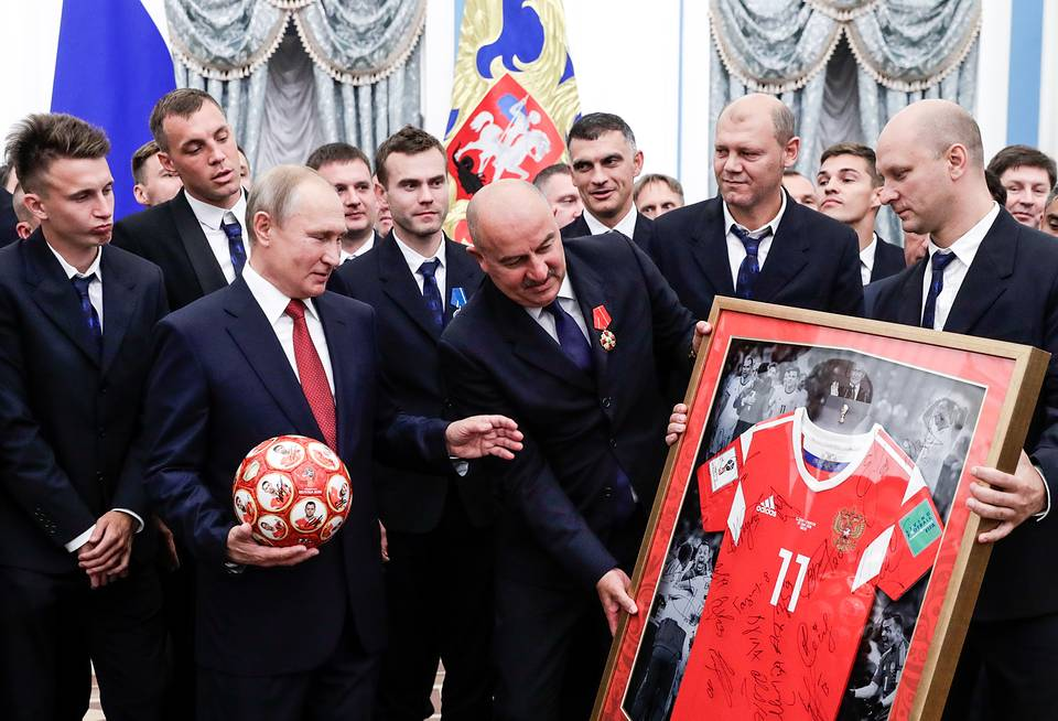 Russian president Vladimir Putin receives a ball and a Number 11 football jersey from the head coach of Russian's national team Stanislav Cherchesov and Russian football players  Mikhail Metzel/TASS